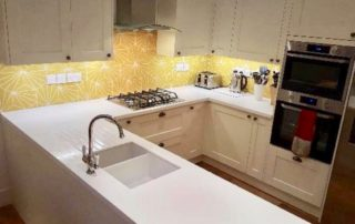 Corian white solid surface kitchen worktop fitted seamlessly round 3 sides